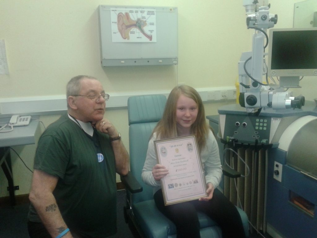 Evie receiving her certificate for funds raised by her baking